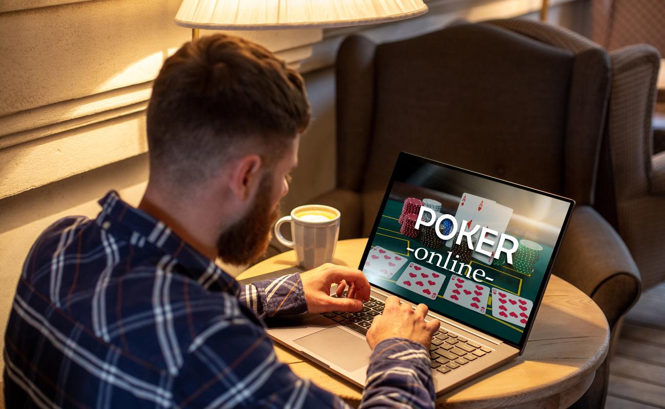 A man plays an online casino poker game on a laptop.