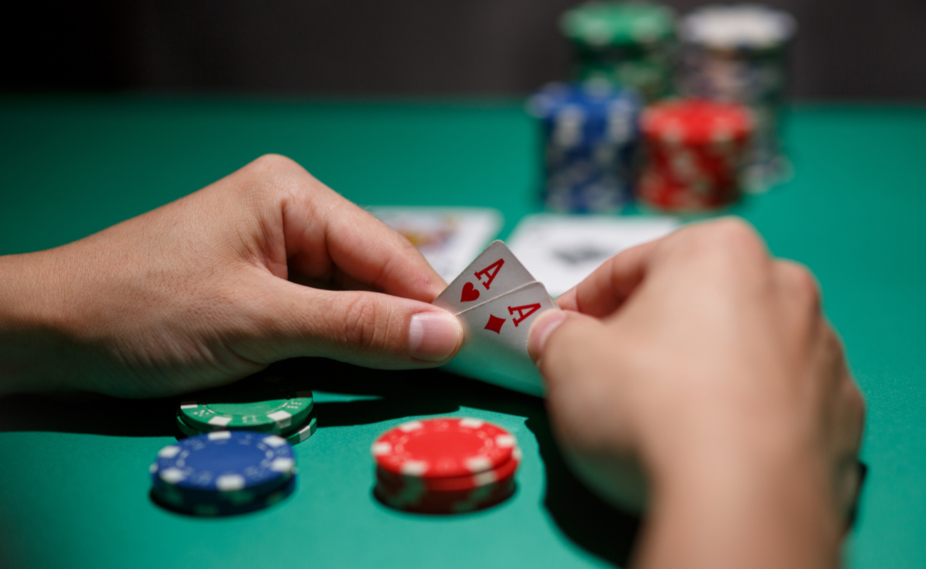 Close-up of a man looking at his poker hand with three stacks of casino chips in front of him.