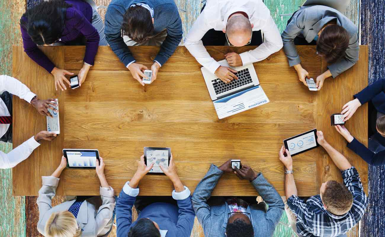 A group of people sitting around a table using various technological devices.