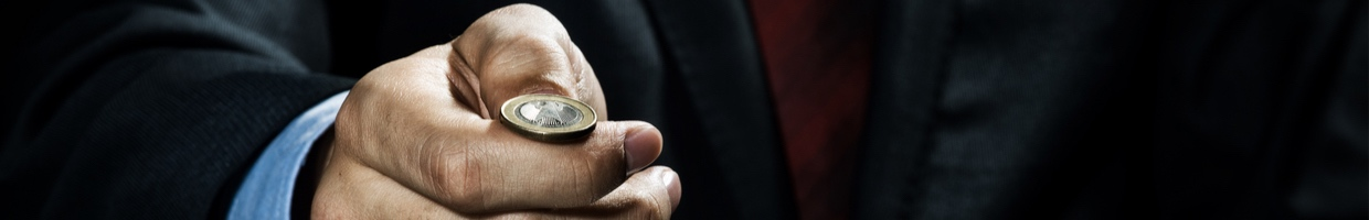 Close-up of a businessman about to toss a coin.
