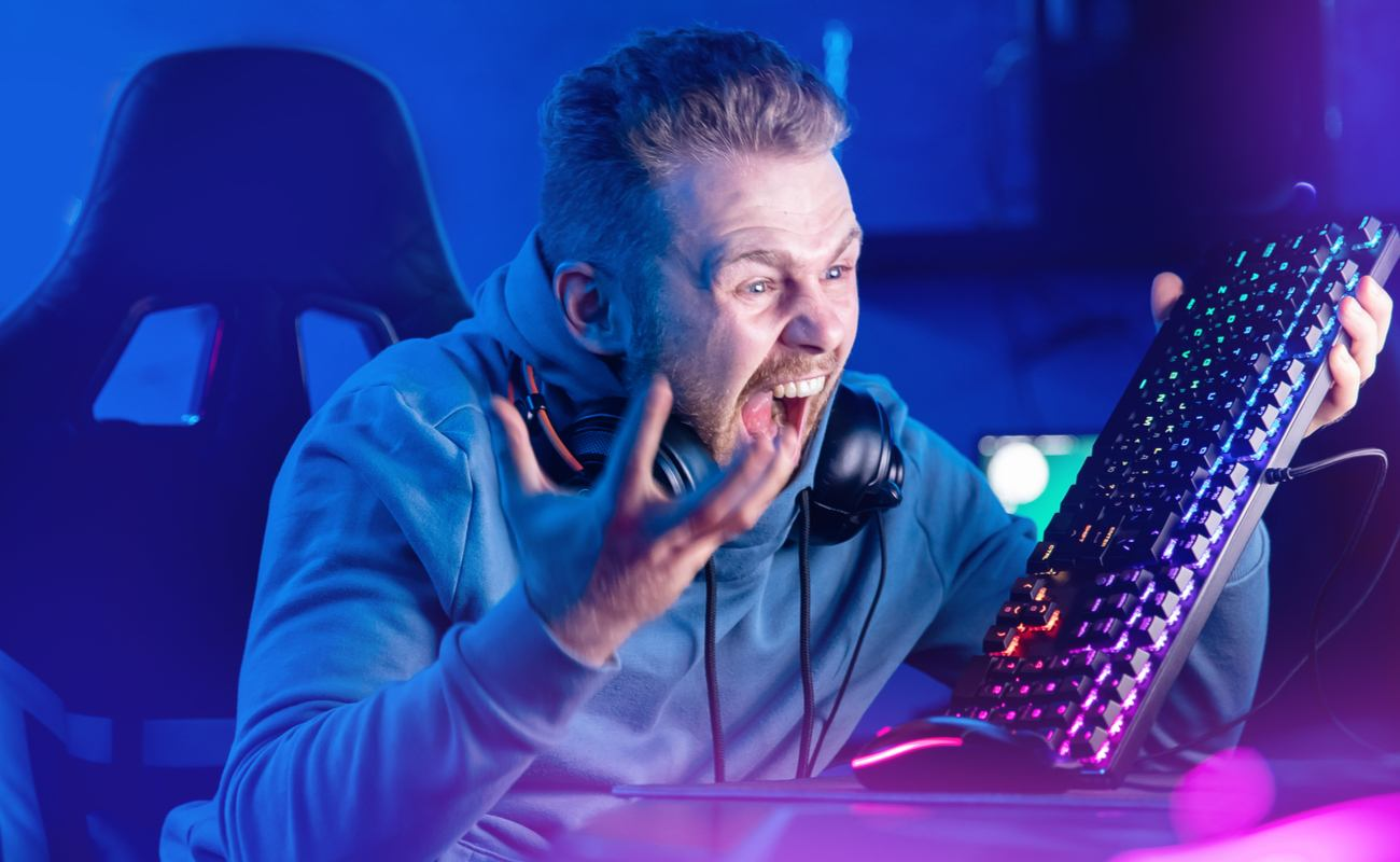 An angry gamer raises his keyboard in frustration.