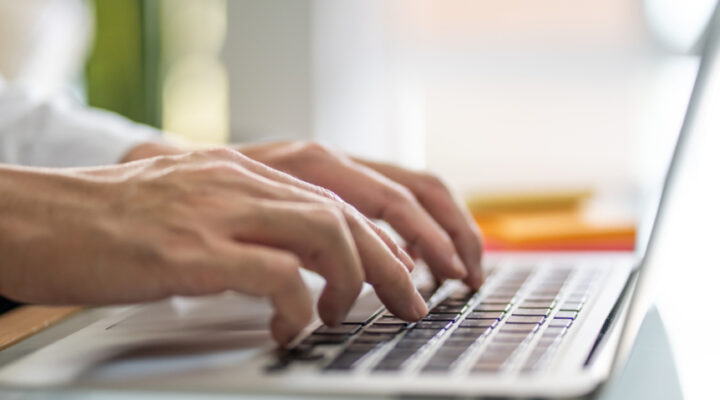 Close-up of a man's hands typing on a laptop.