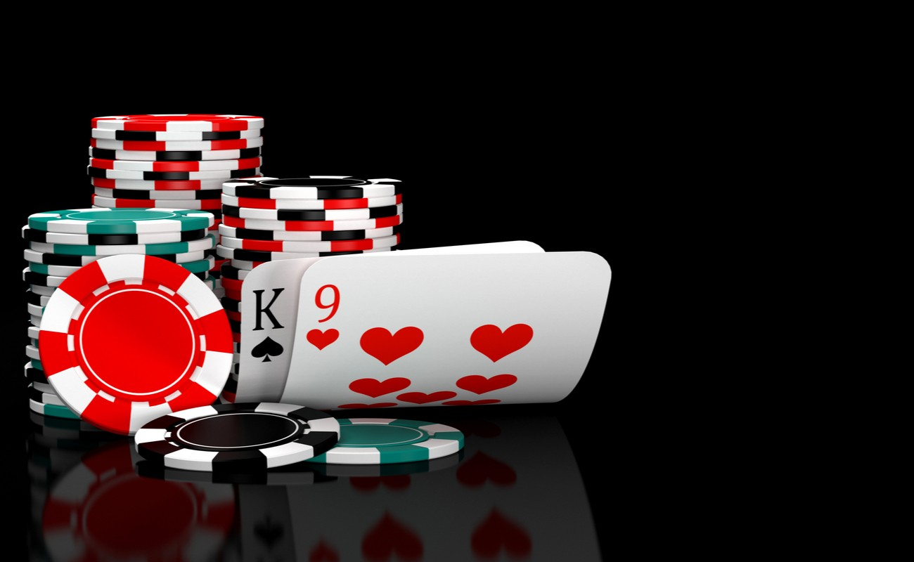 Baccarat cards and casino chips against a black background.
