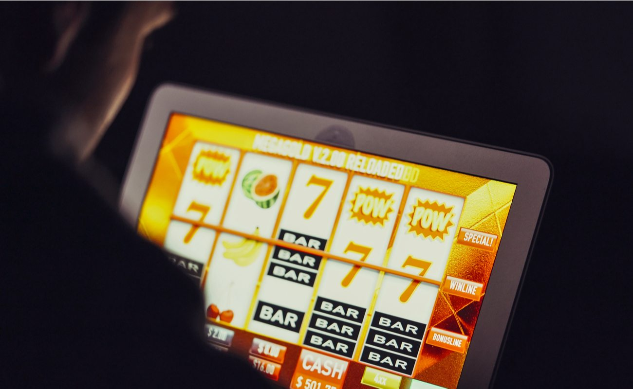 Man playing an online slot on a tablet device.
