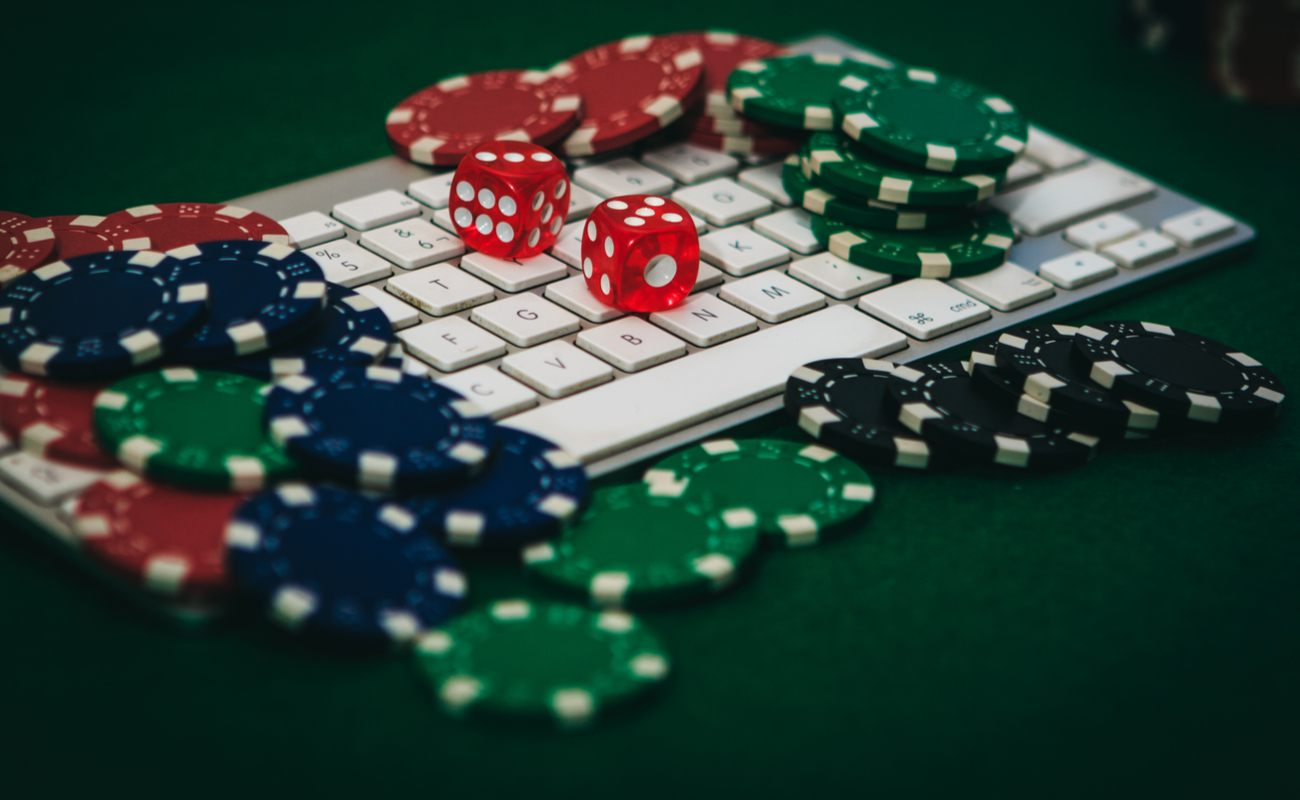 Casino chips and dice sit on top of a keyboard.