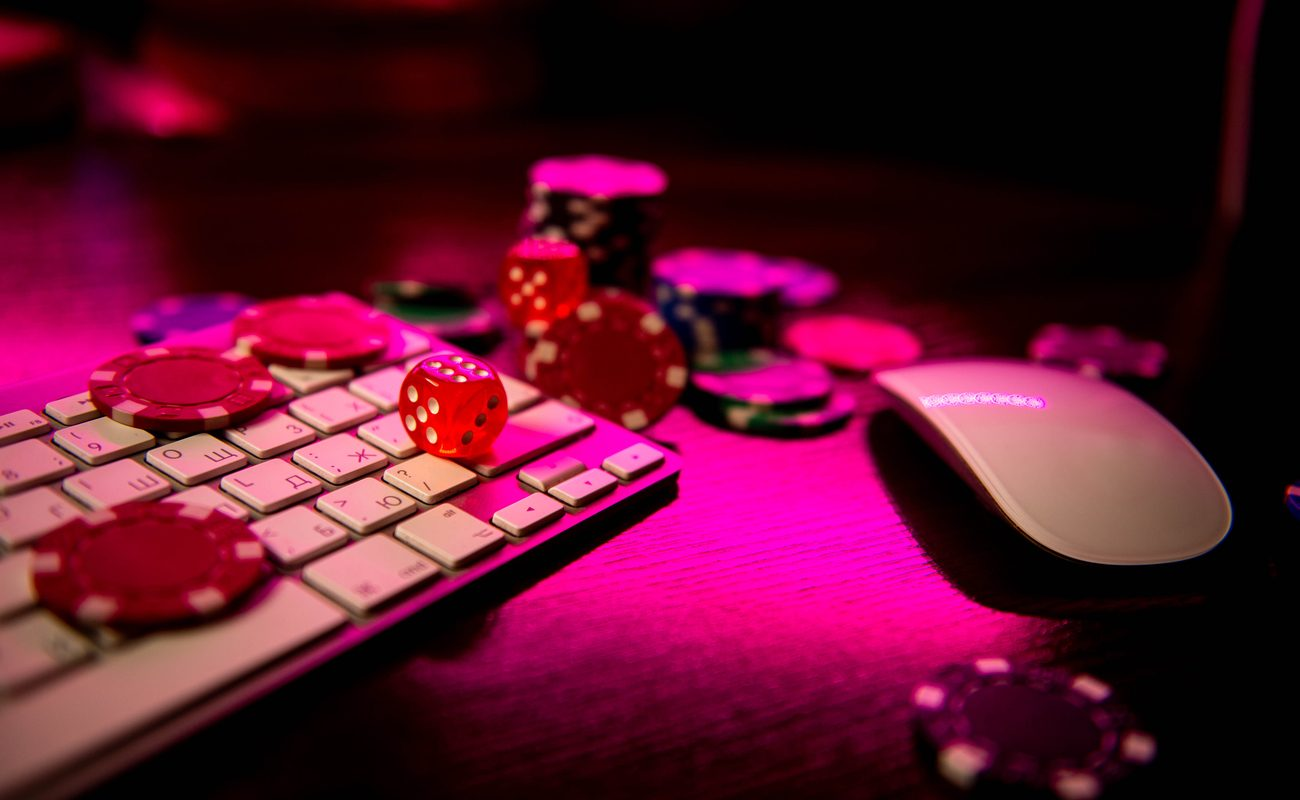 A keyboard and mouse covered with dice and casino chips.