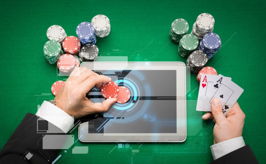 Man holding a casino chip with playing cards above a tablet device.