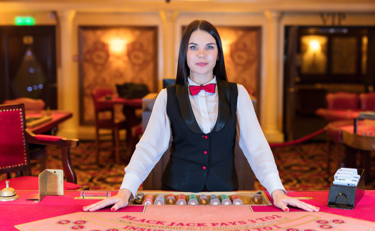 A woman dealer in white shirt, navy waistcoat and red bow tie stands at a blackjack table.