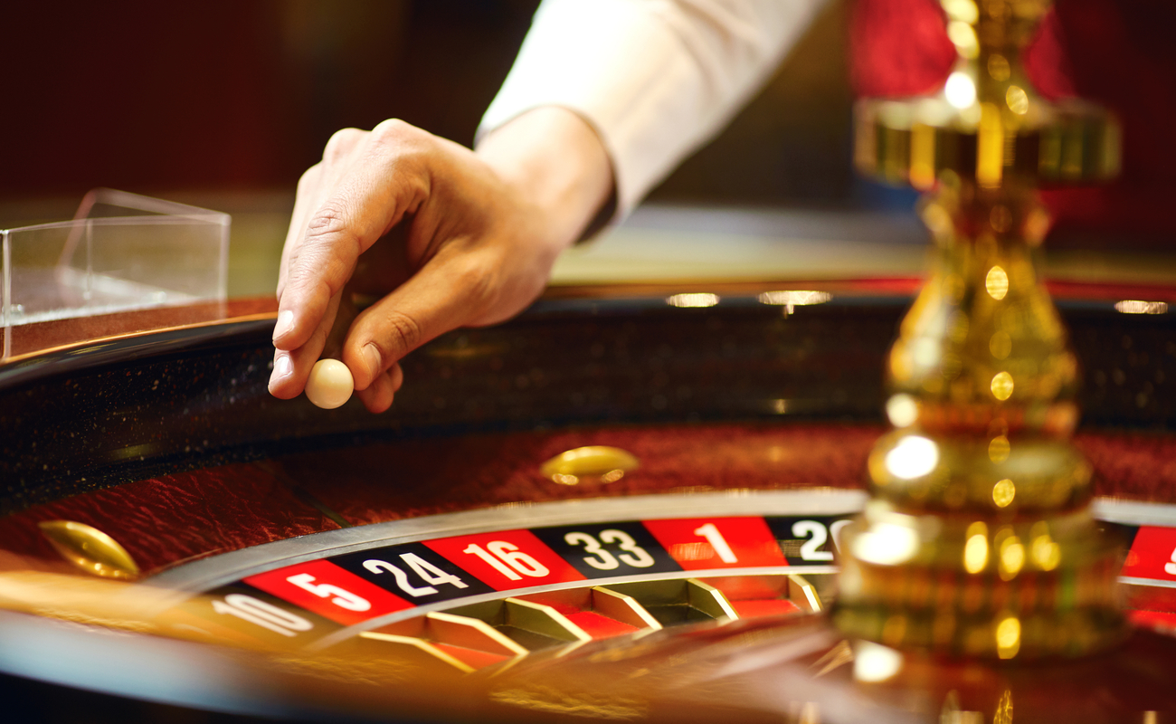 Close-up of a casino dealer about to place a ball on a roulette wheel.