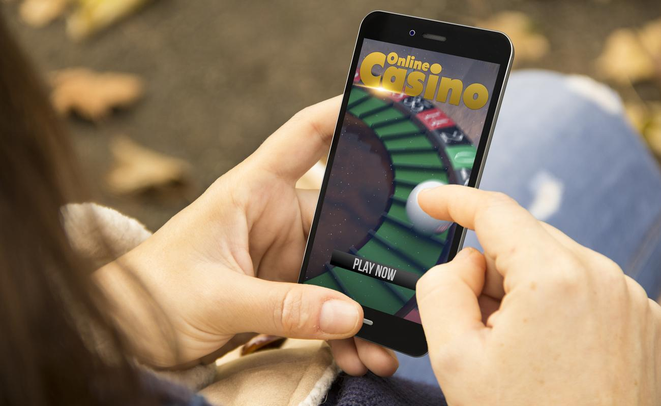 A woman playing online casino games on her smartphone.