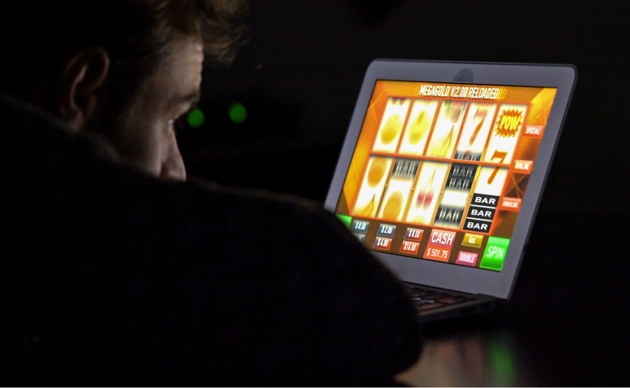 A man plays online slots on a laptop at night.