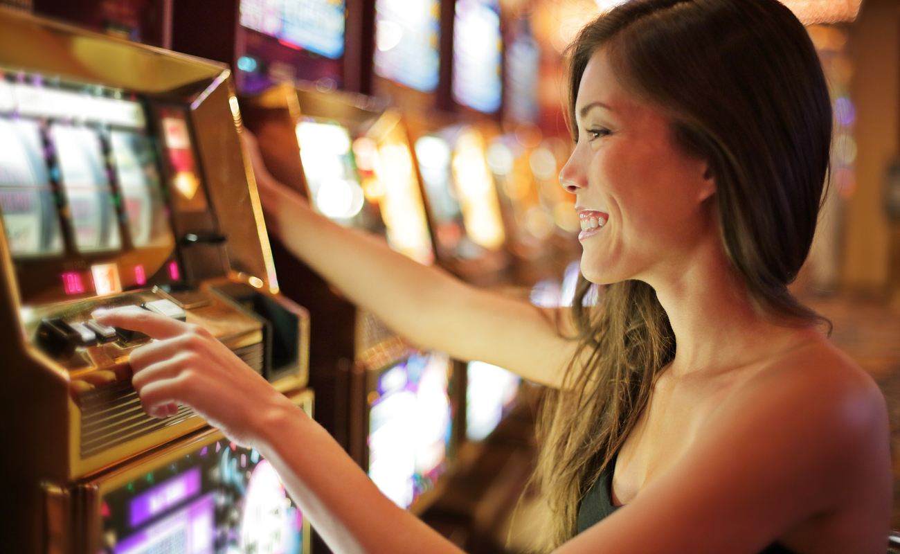 A happy woman playing a slot machine at a land-based casino.