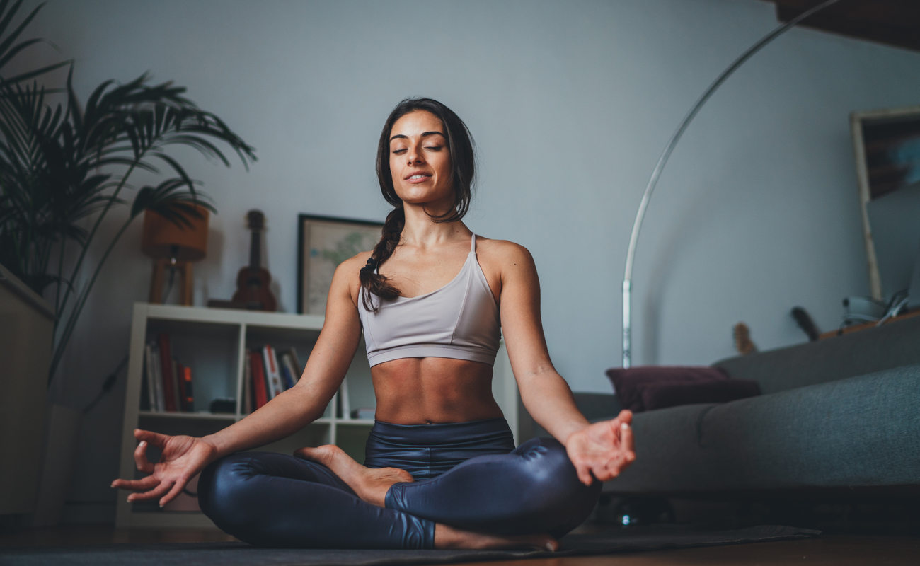 A woman meditating in her living room.