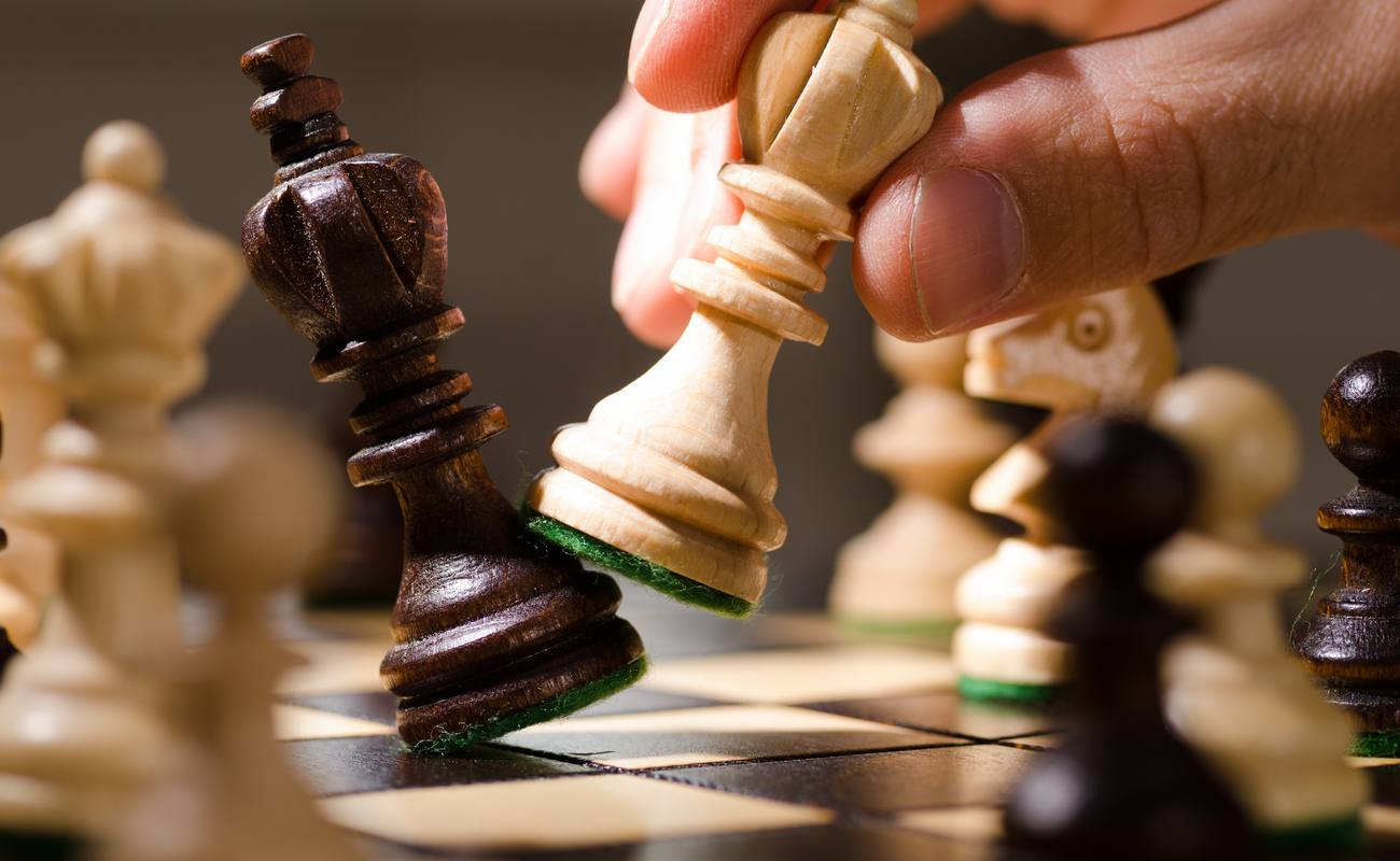 A hand with a chess piece knocks over an opponent's king, indicating 'checkmate.'
