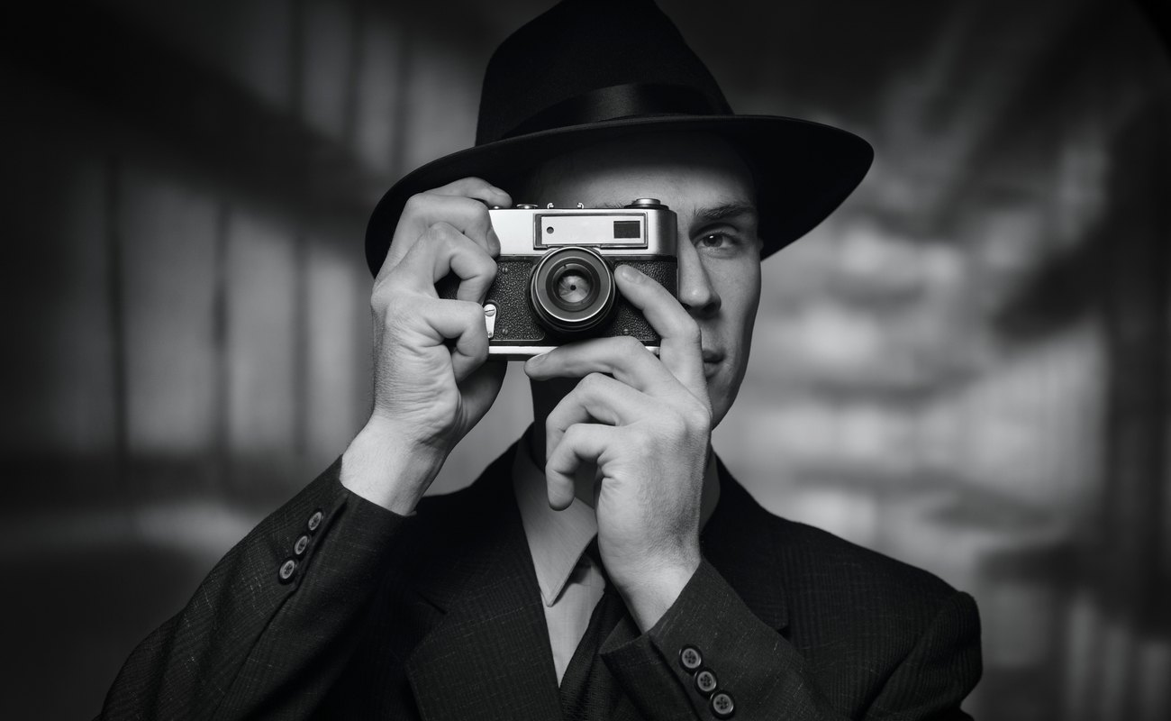 Black-and-white image of a man in a 1950s-style suit and hat taking a picture.