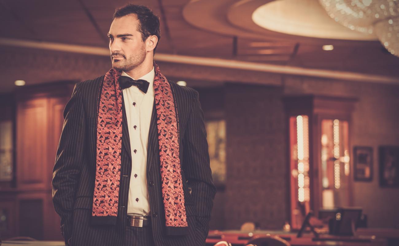 Handsome man wearing suit in luxury casino interior.
