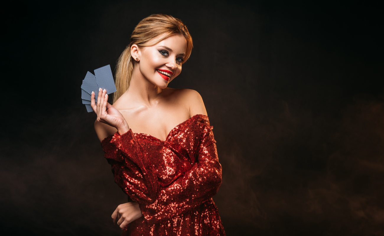 Woman with long hair in a red sequined dress holding playing cards against a black background.