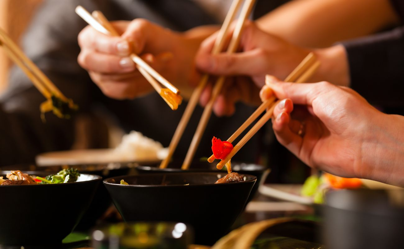 People eating out of bowls with chopsticks at an Asian restaurant.