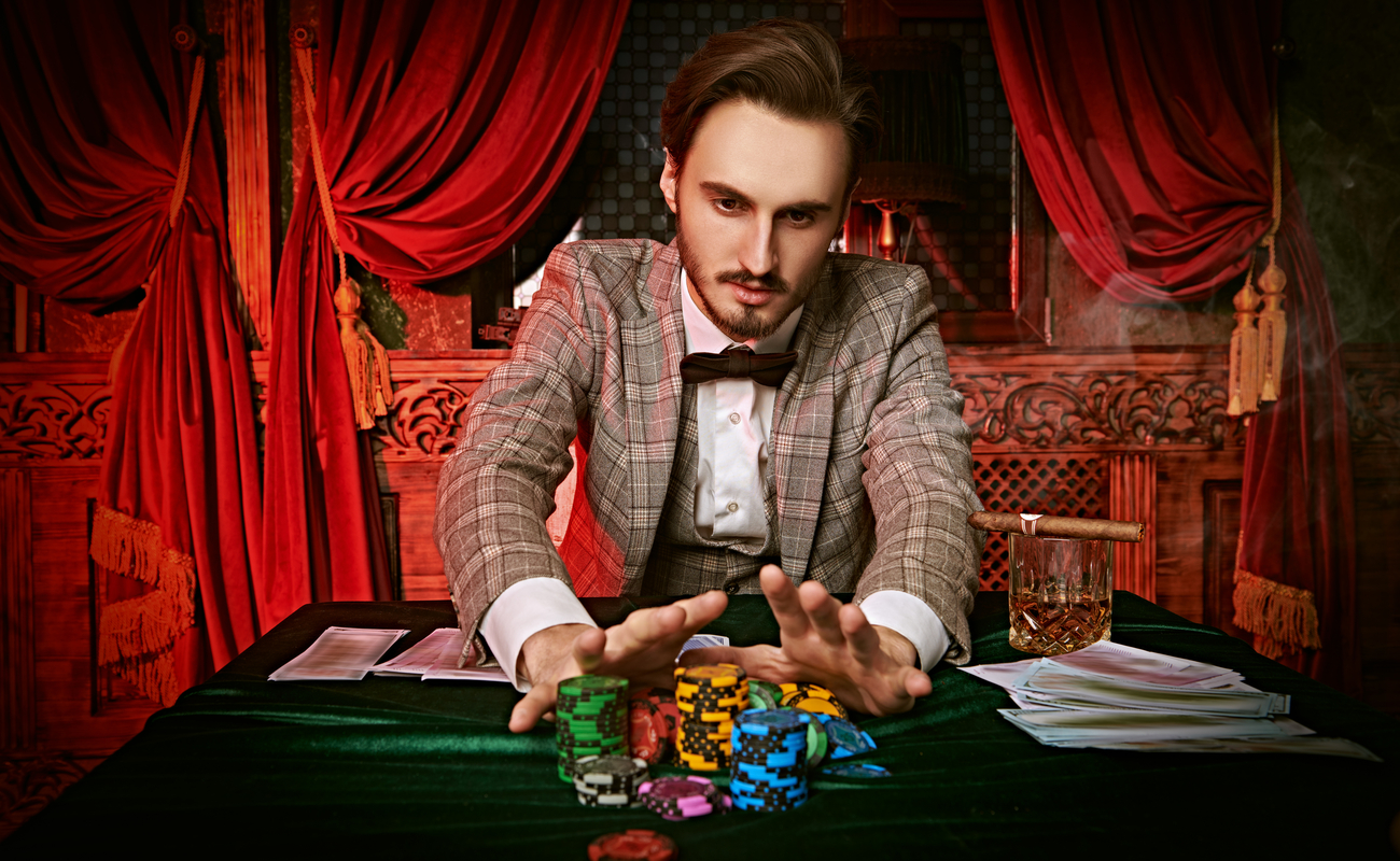 A well-dressed man pushes a pile of casino chips forward with lush red drapes in the background.