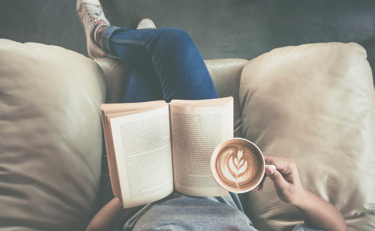 Top view of a woman reading a book and drinking coffee.