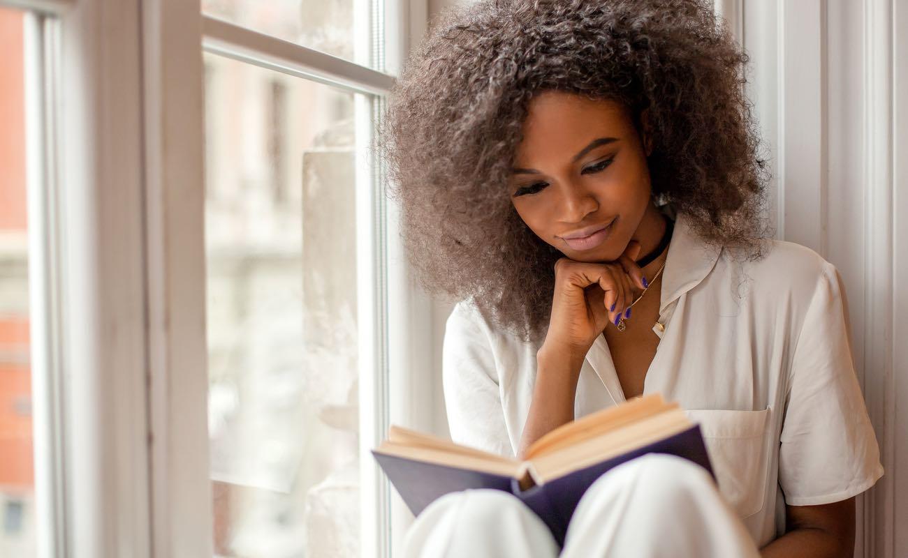 Women sitting on a windowsill, reading a book.