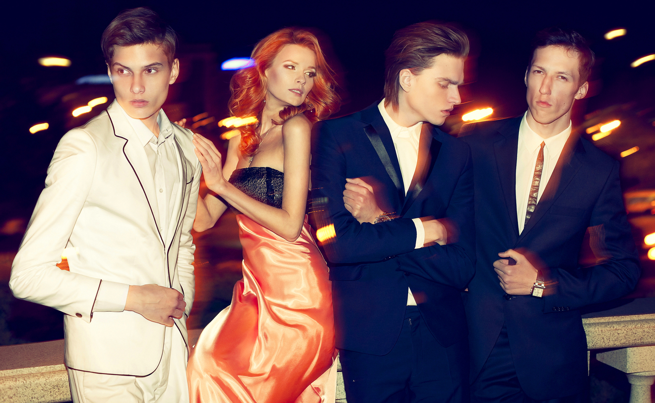 Fashion-conscious men and women pose on a balcony.
