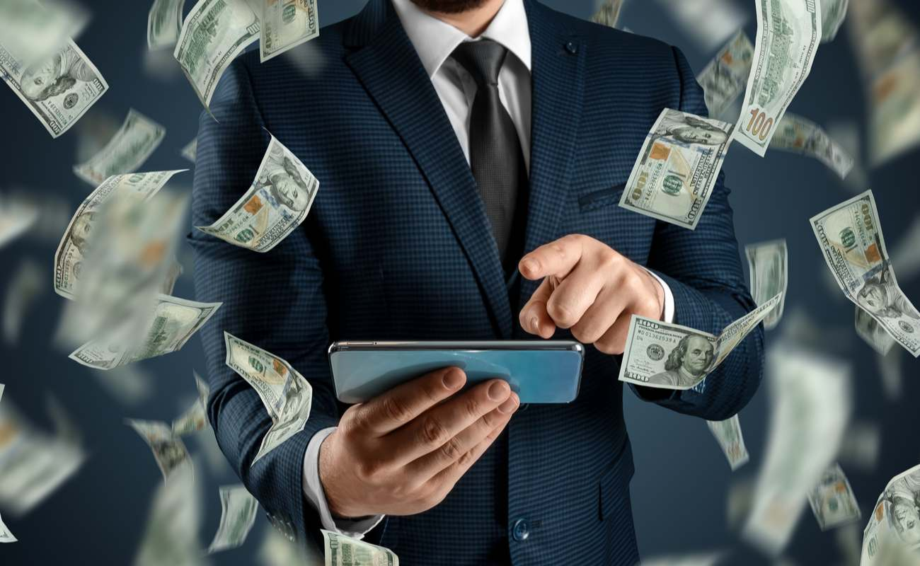 Man in a suit playing games on his mobile phone with 100-dollar bills floating around him