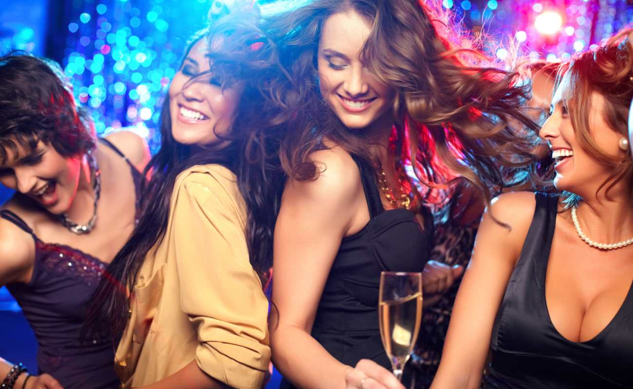 Four women drinking and dancing at a nightclub.