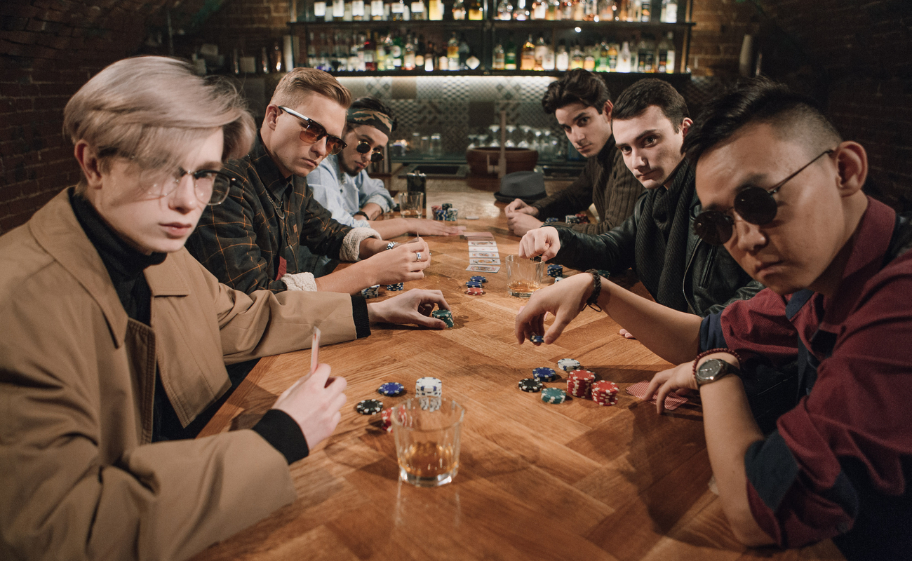 Six men playing poker at a wooden table with a bar in the background.