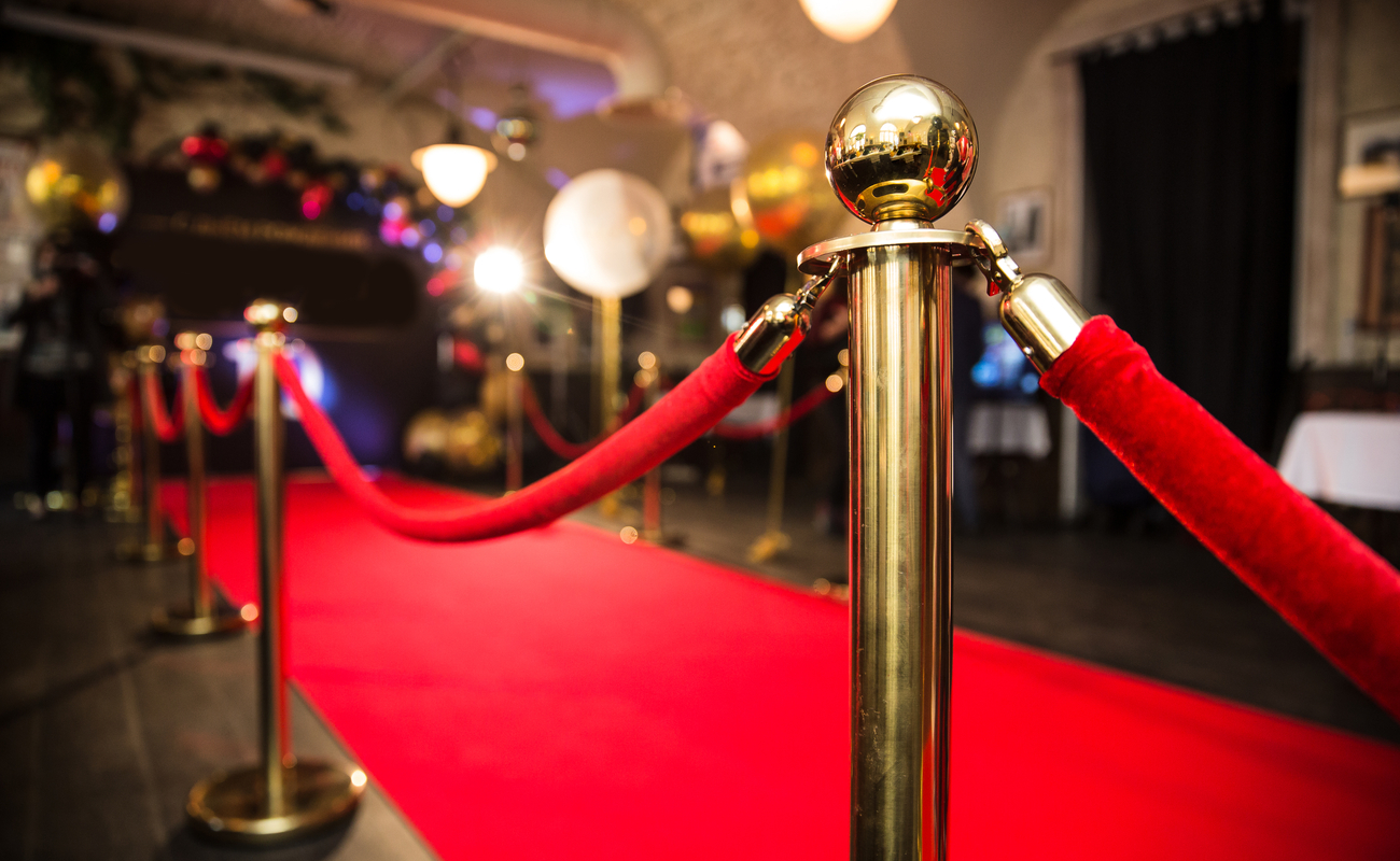 A red carpet and gold stanchions at a celebrity event.