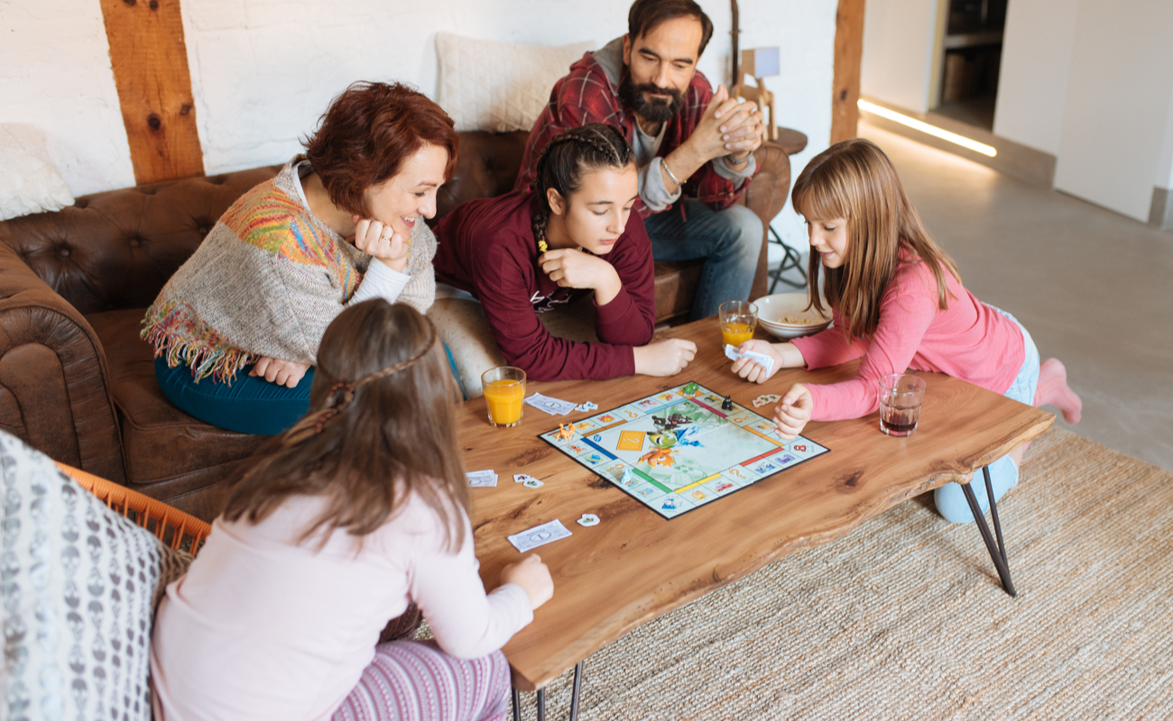 A family playing a board game around a coffee table.