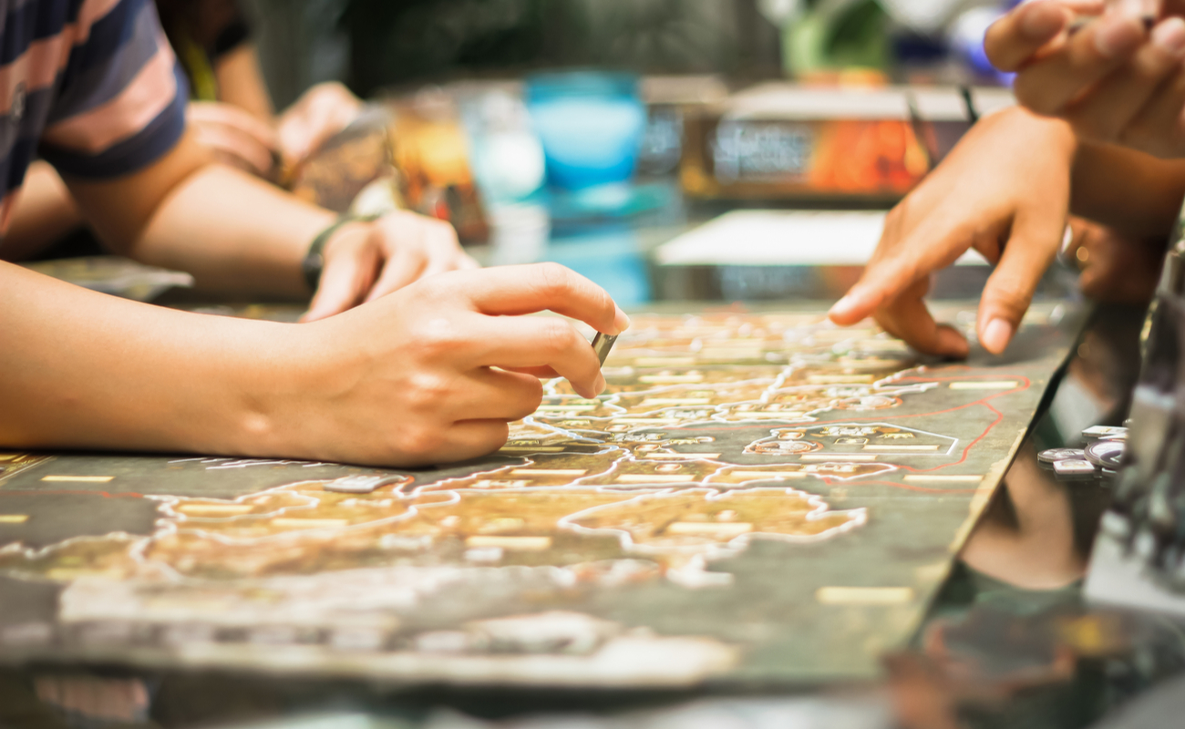 Close-up of people playing a board game.