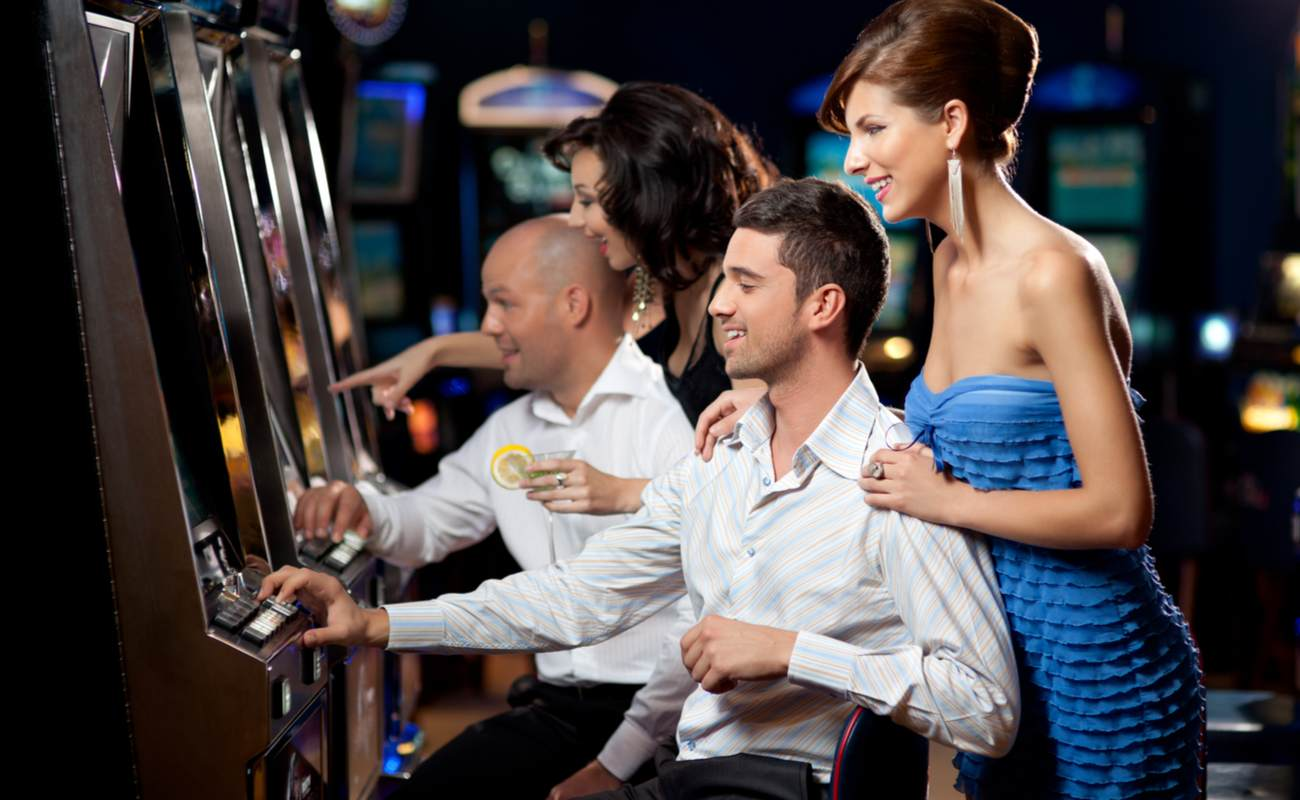 Two couples have a good time playing slots.