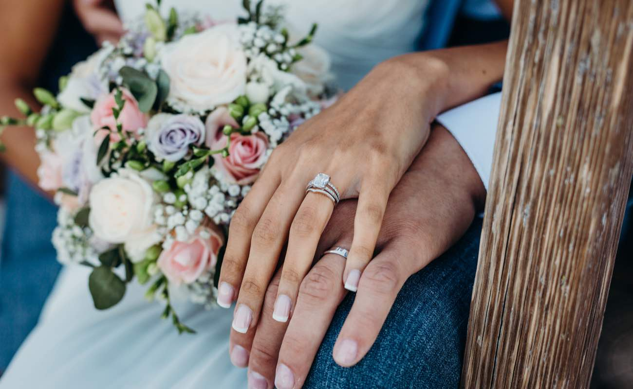 Close-up of a wedding couple's hands and a bouquet of flowers.