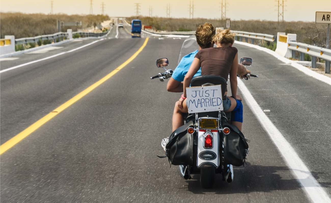 """Couple riding on a motorbike on the highway with a """"Just Married"""" sign."""