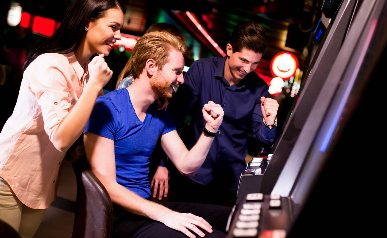 A group of friends cheer after a win at a slot machine.