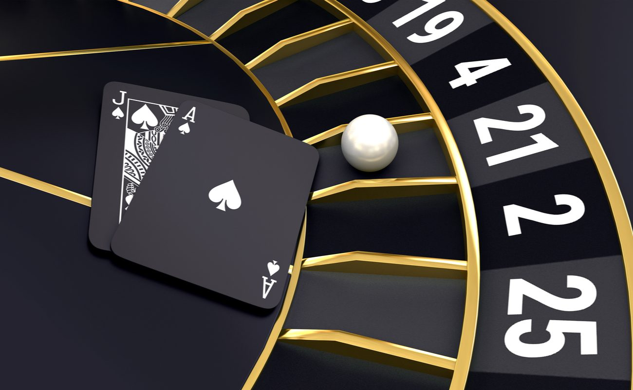 3D concept of a black roulette wheel with a ball, an Ace and a Jack playing card on it.