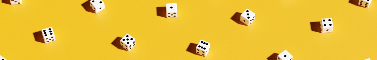 Arrangement of black and white dice against a yellow background.