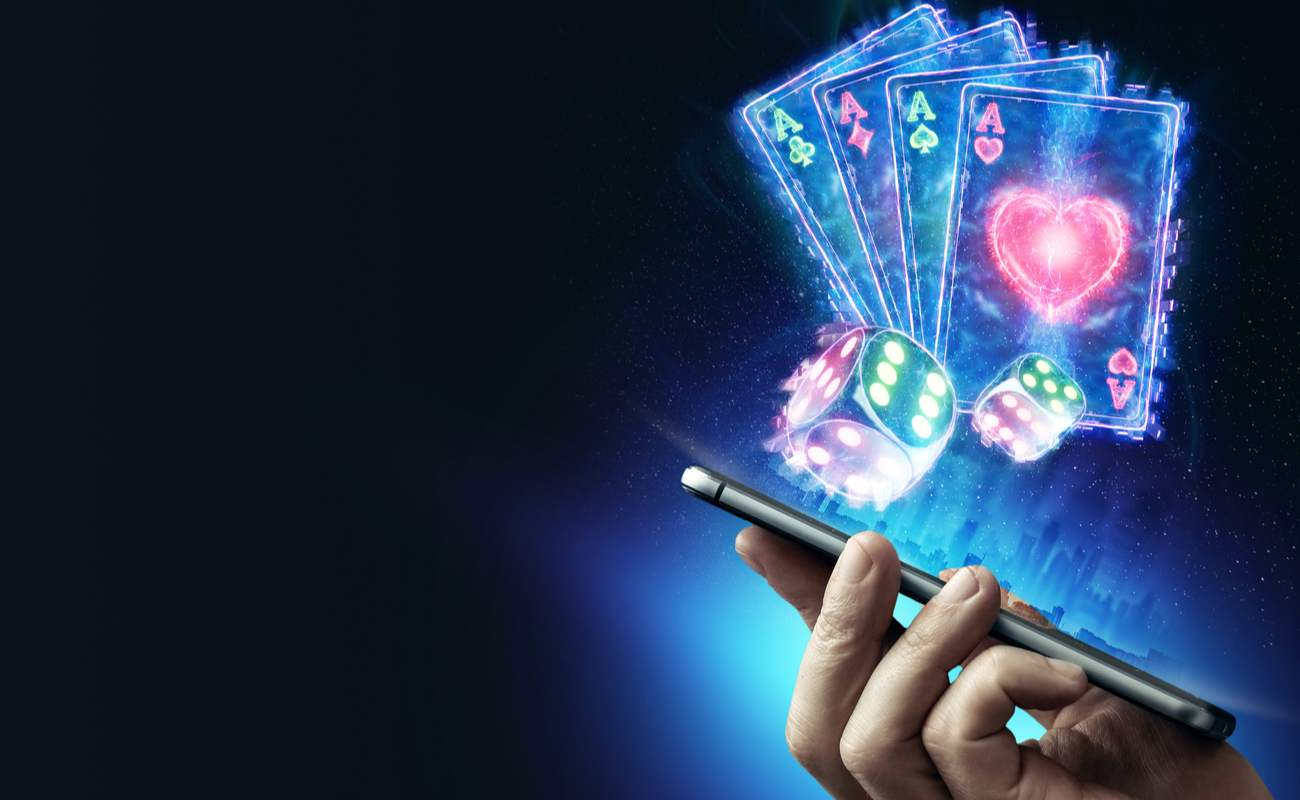 Online casino concept with a hand holding a smartphone with dice and playing card symbols above the screen.