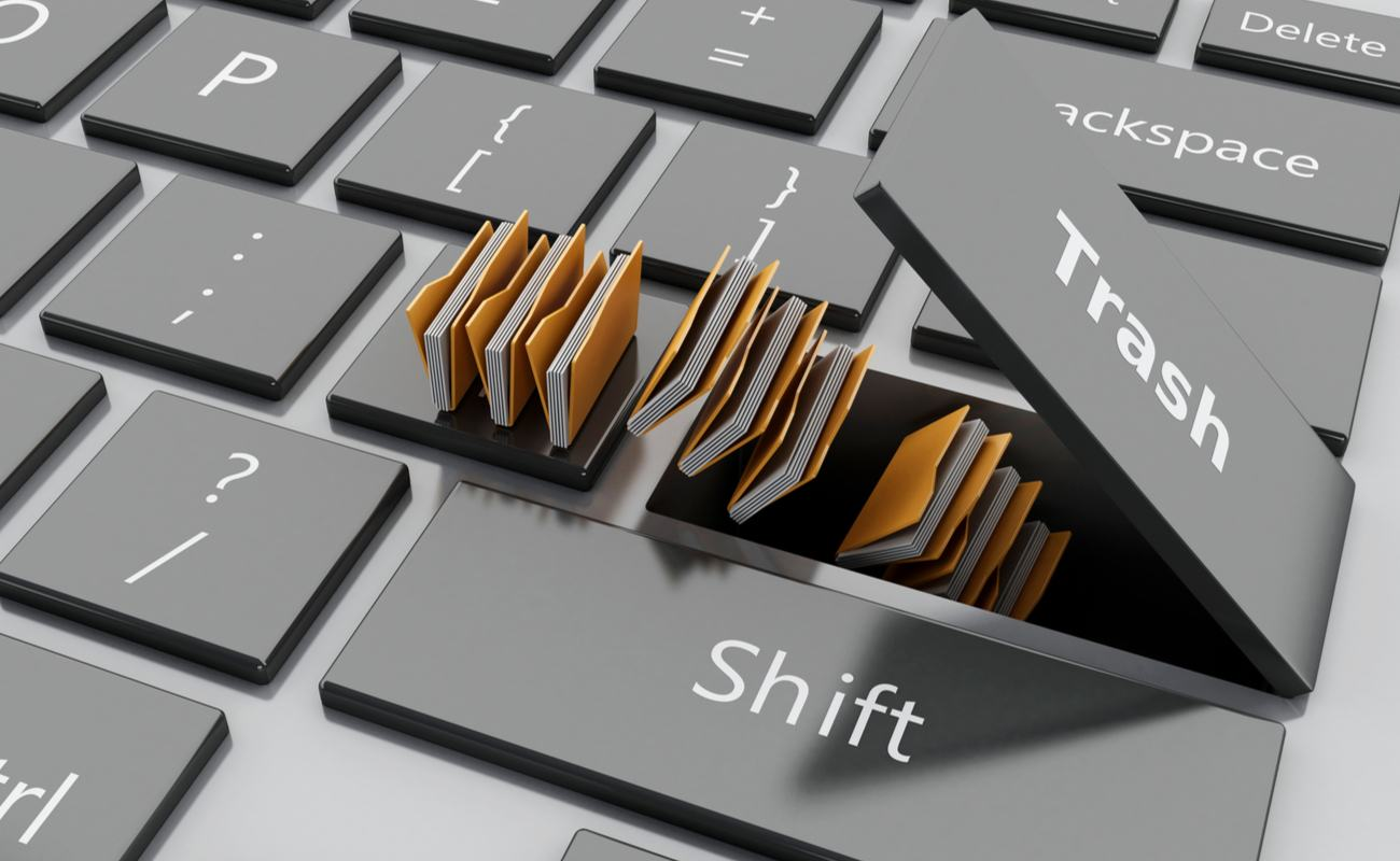 A 3D-rendered illustration of computer files disappearing into a keyboard under the Trash key.