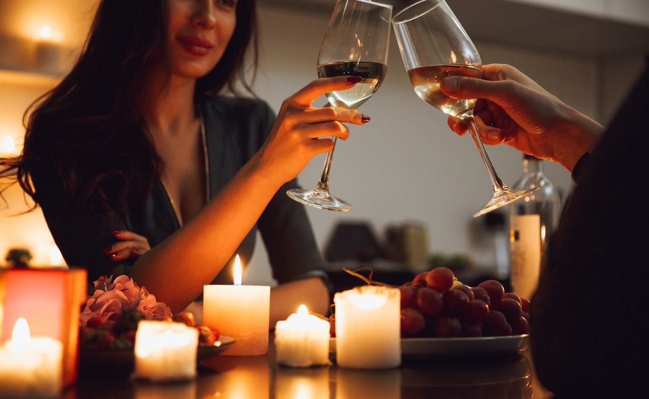 A couple having a romantic candlelight dinner at home, drinking wine, toasting.