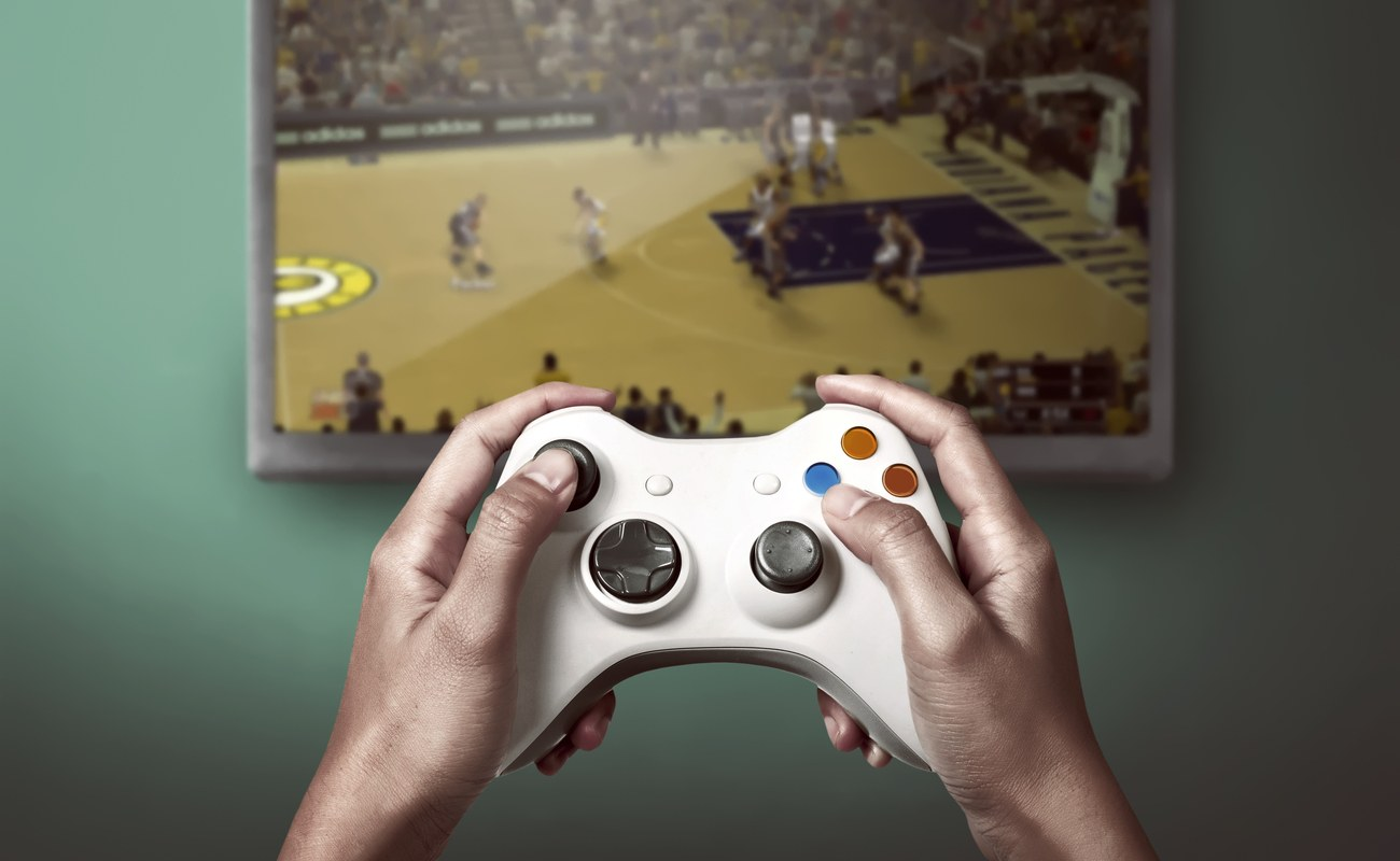 Person playing a basketball video game with a white controller