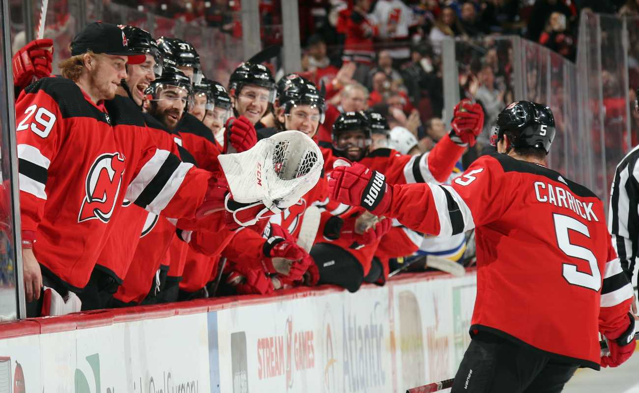 Connor Carrick #5 of the New Jersey Devils celebrates his goal with teammates