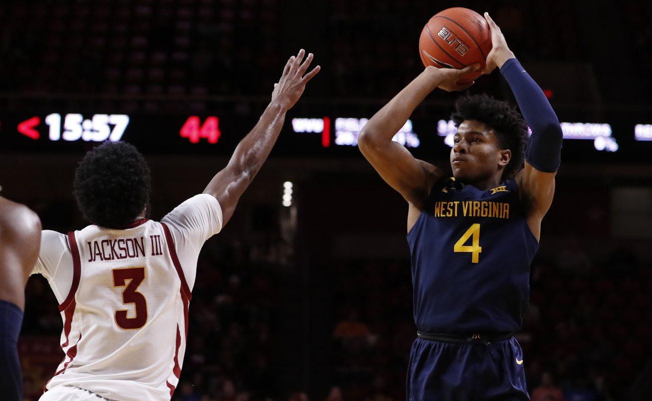 Miles McBride of  West Virginia Mountaineers shoots basketball as Tre Jackson of Iowa State Cyclones blocks