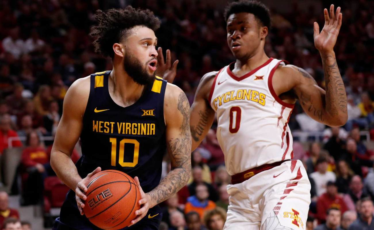 Jermaine Haley of West Virginia Mountaineers passes the ball as Zion Griffin of Iowa State Cyclones defends