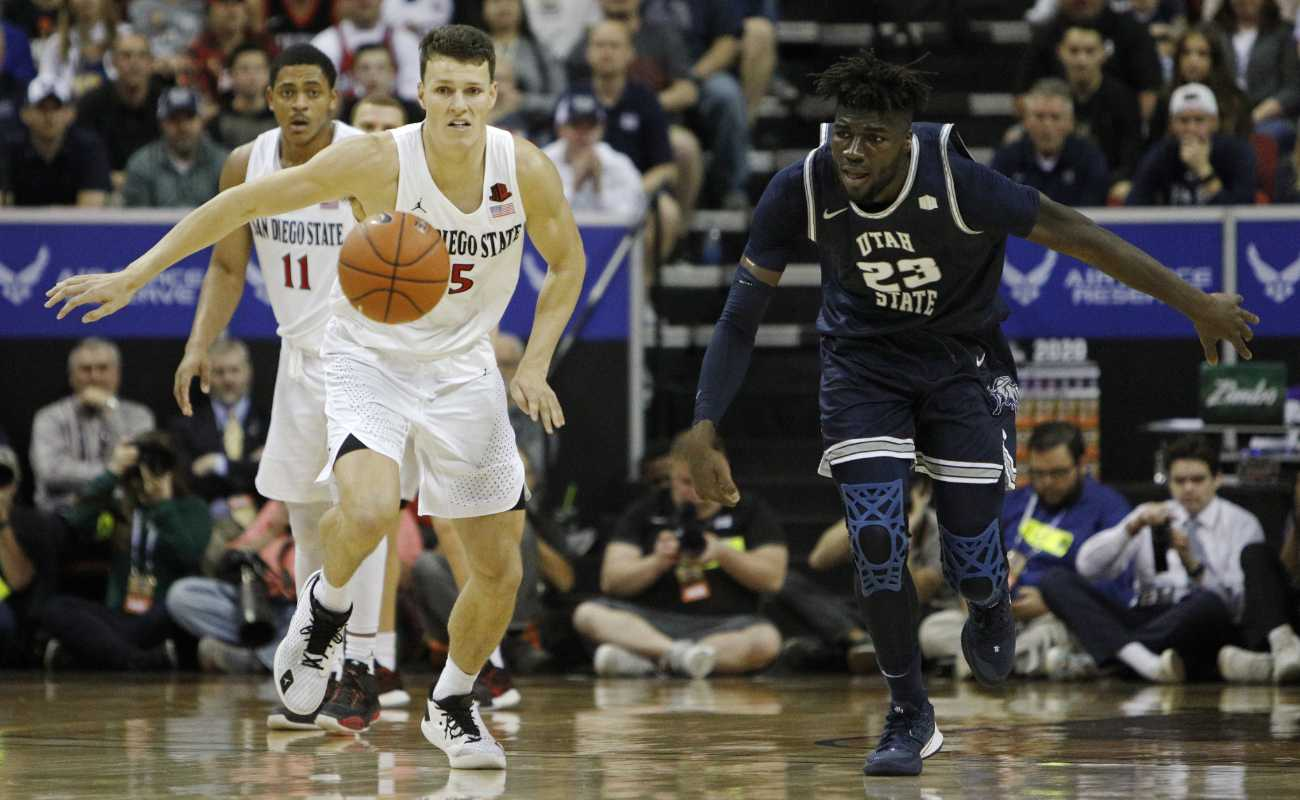 Yanni Wetzell of San Diego State Aztecs and Neemias Queta of Utah State Aggies go for the loose ball during the championship game