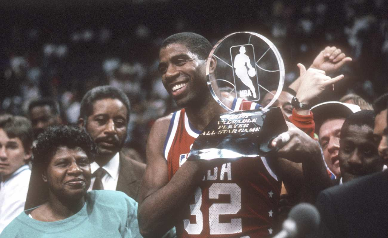 Earvin Magic Johnson #32 of West NBA All-Stars holds up the Most Valuable Player trophy 1990