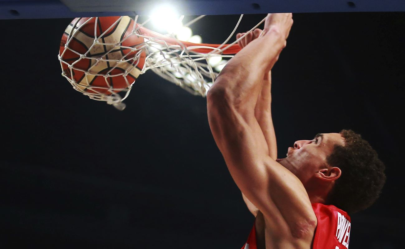 Dwight Powell flies to dunk basketball in the net during a game.