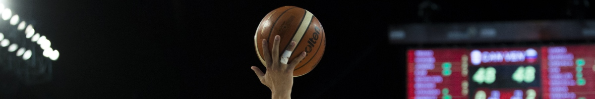 Player's hand lifts basketball in dark background.