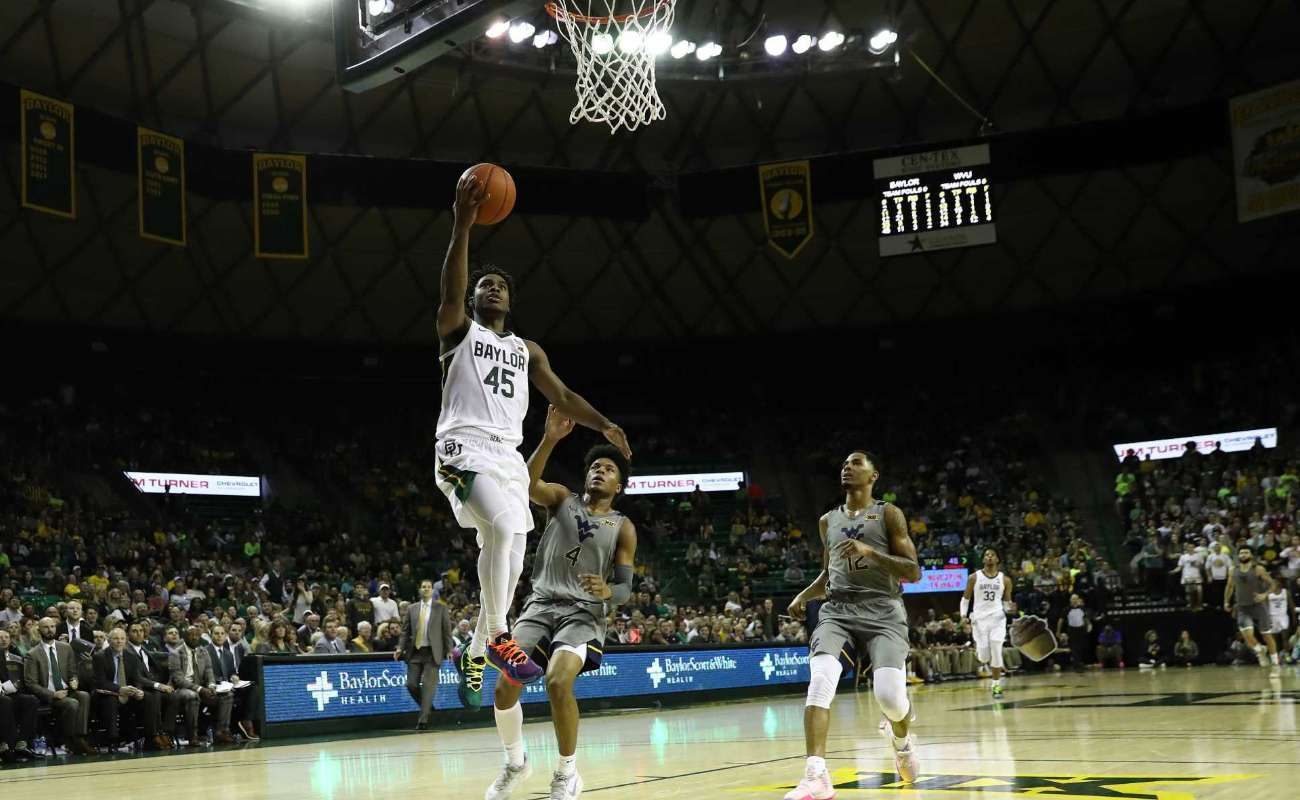 Davion Mitchell of Baylor Bears takes a shot against Miles McBride of West Virginia Mountaineers